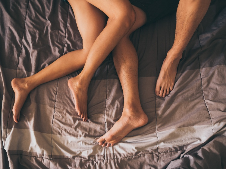 przeplatające się nogi zakochanych na łóżku
