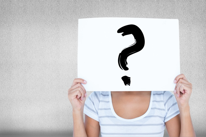 kobieta z kartkąpapieru na której jest znak zapytania