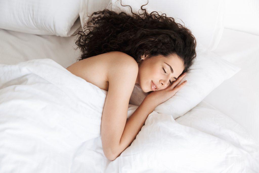 młoda kobieta śpiąca w łóżku