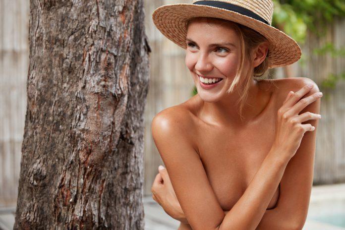 młoda kobieta zakrywająca piersi