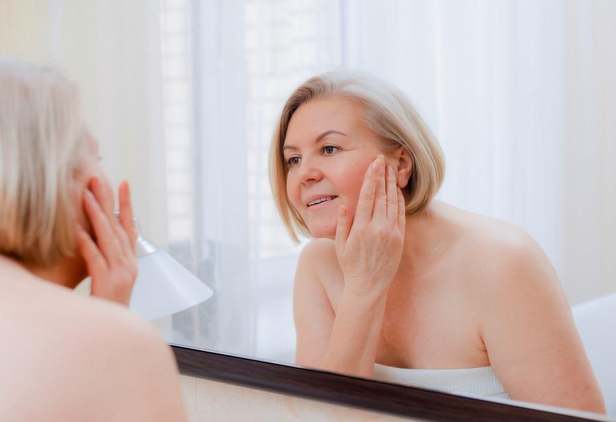 kobieta w wieku około 60 lat z cerą bez zmarszczek przegląda się w lustrze